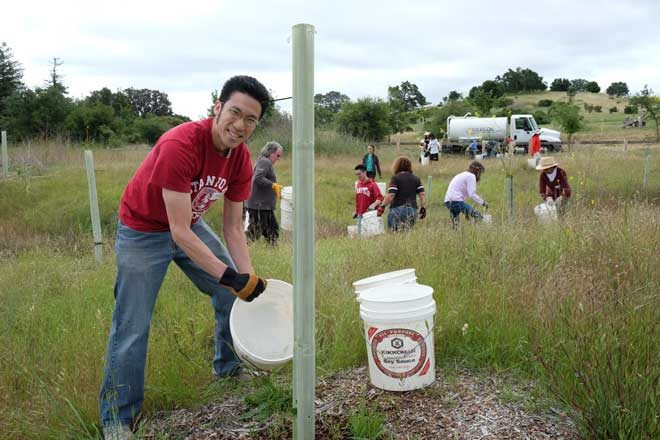 Magic volunteers work a bucket brigade from a tank truck into the field to water young trees. Photo: courtesy of Magi